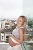 Pregnancy with the urban landscape on the balcony Royalty Free Stock Photos