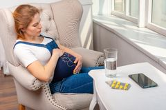 Illness during pregnancy. Woman sitting at home and taking medical drugs. Pregnancy vitamins and medications. Pregnant girl in denim overalls sitting in royalty free stock photography