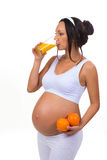 Pregnancy and vitamins. Pregnant woman and oranges and fresh juice. Stock Photography