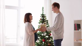 Husband giving christmas present to pregnant wife stock video