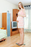 Pregnancy woman  on bathroom scale Stock Photo
