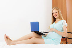 Pregnancy woman with laptop on white sheet royalty free stock image