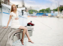 Pregnancy woman sitting at port Stock Photography