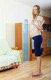 Pregnancy woman standing on bathroom scales. Serious pregnancy woman standing on bathroom scales at living room royalty free stock images