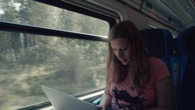 Pregnancy Woman Working with Laptop on a Train. Pregnancy Woman Working with Smartphone and Laptop Computer on a Train stock footage