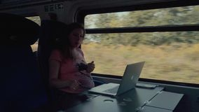 Pregnancy Woman Working with Smartphone on a Train stock video footage