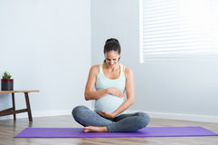 Pregnancy yoga exercise. Pregnant woman sitting in lotus position on exercise mat and touching her belly. Pregnant athletic woman ready for yoga prenatal stock photos