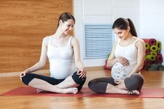 Pregnancy Yoga, Fitness concept. Two beautiful young pregnant yoga models working out indoor. Pregnant smiling fitness women sitti royalty free stock image