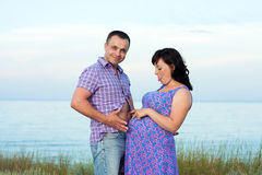 Pregnancy. Young loving couple on the beach. Stock Images