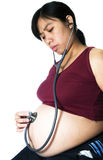 Pregnant. A pregnant women listen her tummy with stethoscope Royalty Free Stock Photos