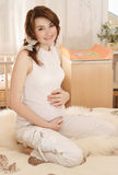 Pregnant. Smiling a pregnant young woman sitting on the couch Stock Photo