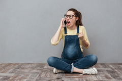 Pregnant angry screaming woman talking by mobile phone. Image of pregnant angry screaming woman wearing glasses sitting isolated over grey wall. Talking by Stock Image