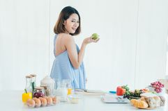 A pregnant Asia beautiful girl holds the green apple royalty free stock photos