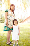 Pregnant Asian mother and her daughter Stock Images