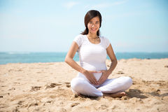 Pregnant asian woman doing yoga in the sea shore Stock Images