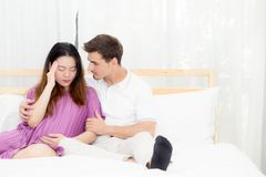 Pregnant asian woman belly acheand feel sick and husband with take care. Pregnant asian women belly acheand feel sick and husband with take care on bedroom royalty free stock photography