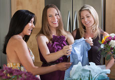 Pregnant With Baby Clothes. Happy pregnant woman gift from friends for a baby shower Stock Image