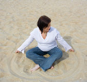 Pregnant on the beach. Pregnant woman sitting on sand Stock Image