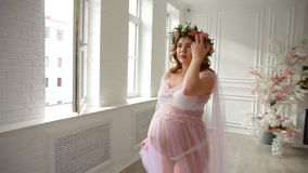 Pregnant beautiful girl in lilac peignoir and floral head wreath is walking on luxury room stock footage