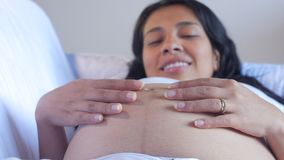 Pregnant beautiful Latin American woman lying in couch caressing her belly with her hands stock video footage