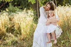 Pregnant beautiful mother  with little blonde girl in a white dress sitting on a swing, laughing, childhood, relaxation Royalty Free Stock Images