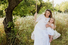Pregnant beautiful mother with little blonde girl in a white dress sitting on a swing, laughing, childhood, relaxation, serenity, Stock Photos