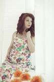 Pregnant beautiful red-haired woman sitting on a window sill at the window Royalty Free Stock Photography