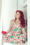 Pregnant beautiful red-haired woman sitting on a window sill at the window. Pregnant cute beautiful red-haired woman sitting on a window sill at the window Stock Images