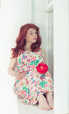 Pregnant beautiful red-haired woman sitting on a window sill at the window. Pregnant cute beautiful red-haired woman sitting on a window sill at the window Stock Photos