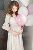 Pregnant beautiful woman with bunch of balloons. Stock Images