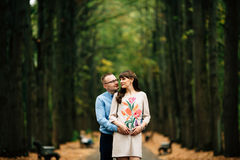 Pregnant beautiful woman and her handsome husband lovely hugging in autumn park. Royalty Free Stock Image
