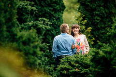 Pregnant beautiful woman and her handsome husband lovely hugging in autumn park. Stock Photo