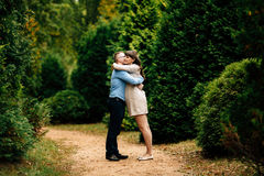 Pregnant beautiful woman and her handsome husband lovely hugging in autumn park. Royalty Free Stock Images