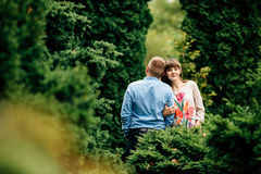 Pregnant beautiful woman and her handsome husband lovely hugging in autumn park. Stock Photos