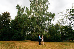 Pregnant beautiful woman and her handsome husband lovely relaxing on nature, have picnic in autumn park. Stock Photos