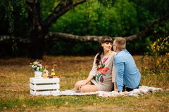 Pregnant beautiful woman with her handsome husband sweetly resting outdoors in the autumn on picnic. Royalty Free Stock Photos