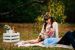 Pregnant beautiful woman with her handsome husband sweetly resting outdoors in the autumn on picnic. Stock Images