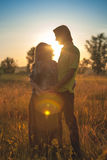 A pregnant beautiful woman with her husband on nature landscape smiling and touching her belly with love and care. Happy. A silhouette of pregnant beautiful stock photo