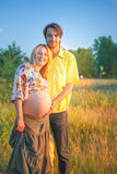 A pregnant beautiful woman with her husband on the river bank beach smiling and touching her belly with love and care. Happy coupl Stock Image