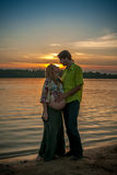 A pregnant beautiful woman with her husband on the river bank beach smiling and touching her belly with love and care Royalty Free Stock Image