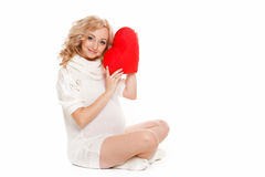 Pregnant beautiful woman holding red heart pillow in her hands isolated on white background Royalty Free Stock Image
