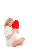Pregnant beautiful woman holding red heart pillow in her hands isolated on white background Stock Images