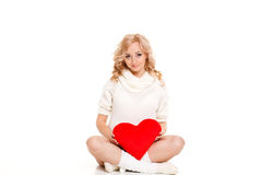 Pregnant beautiful woman holding red heart pillow in her hands isolated on white background Royalty Free Stock Images
