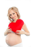 Pregnant beautiful woman holding red heart pillow in her hands isolated on white background Royalty Free Stock Photo