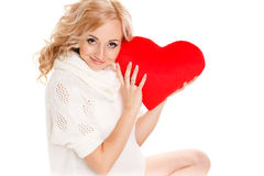 Pregnant beautiful woman holding red heart pillow in her hands isolated on white background Stock Photography