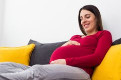 Pregnant beautiful woman holds hands on belly royalty free stock photography