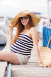 Pregnant beautiful woman on the pier at the sea Stock Photos