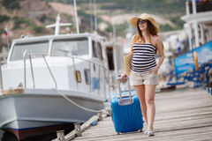 Pregnant beautiful woman on the pier at the sea. Young pregnant woman,brunette,long straight hair, wearing sun glasses and a straw hat,in a short striped dress Royalty Free Stock Image