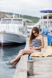 Pregnant beautiful woman on the pier at the sea Stock Photo