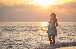 Pregnant beautiful woman is standing on the beach during the sunrise Stock Photo